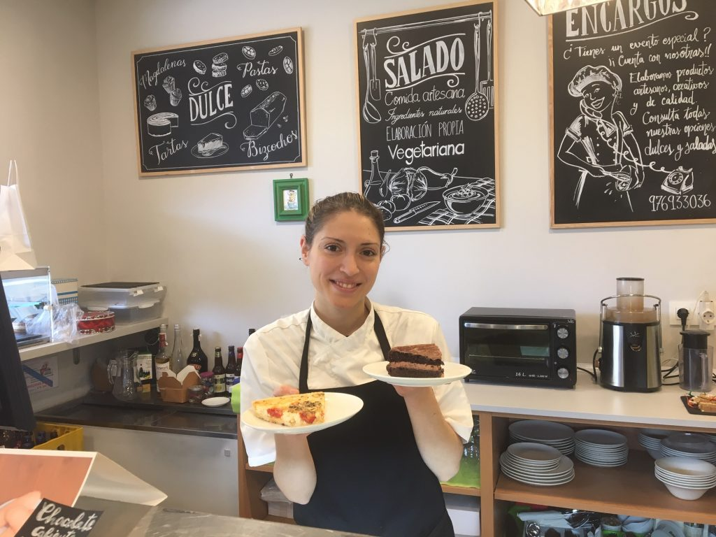 Patricia Blasco, detrás del mostrador de Patipatú con una tarta de chocolate y una quiche